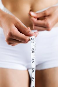 Portrait of woman measuring her slim body. Isolated on white background.